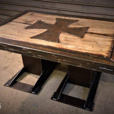 100 x 70 cm Platte bestehend aus 60 x 60mm Vierkantrohrrahmen und aufbereitetem Altholz. Mittig ins Holz eingelassen ein Ironcross. 45 cm hoch auf 200mm Vierkantrohr.
